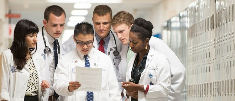 A group of diverse medical students leaning in to read a single document.