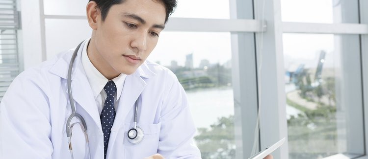 A young doctor in a white jacket looking at a tablet.
