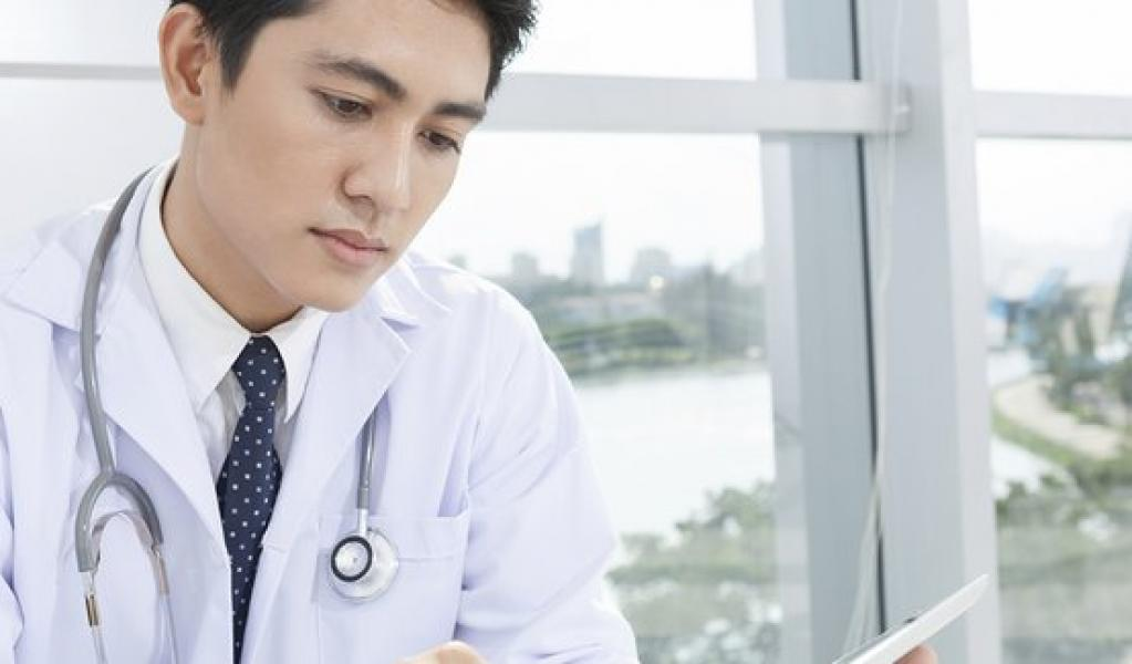 doctor in white jacket looking at tablet
