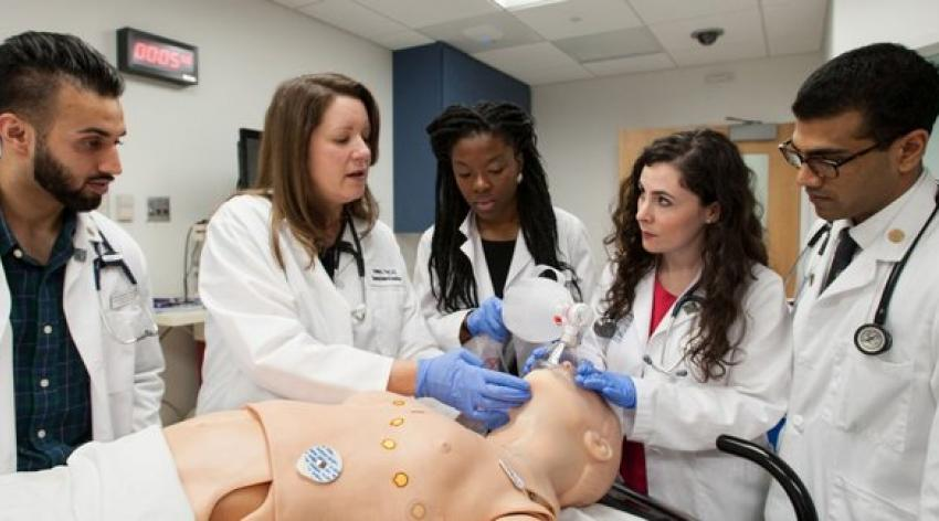 Professor instructs medical students using a simulated patient