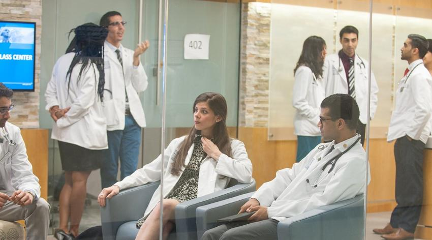 group of medical students conversing in white coats in meeting center