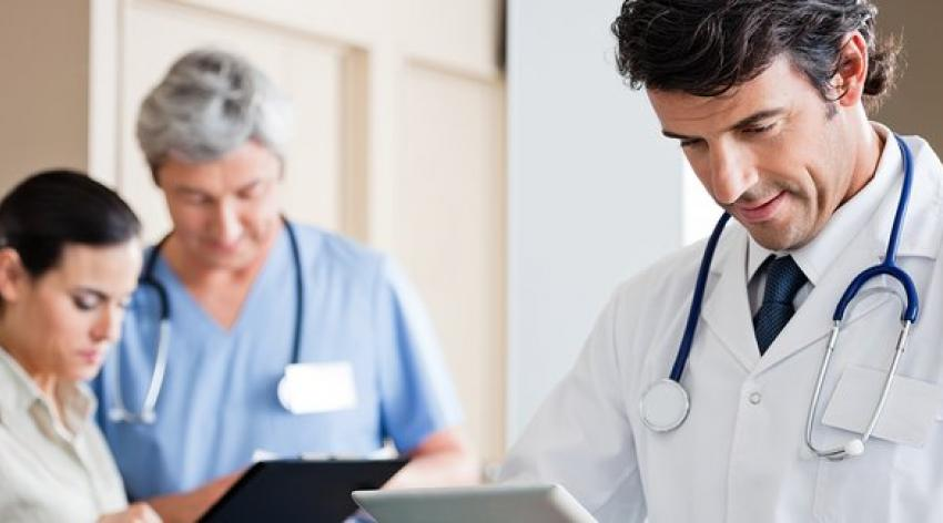 Male doctor holding digital tablet with colleague and receptionist standing in background